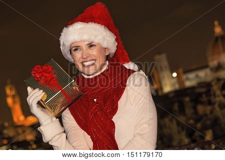 Young Woman With Christmas Present Box In Florence Looking Aside