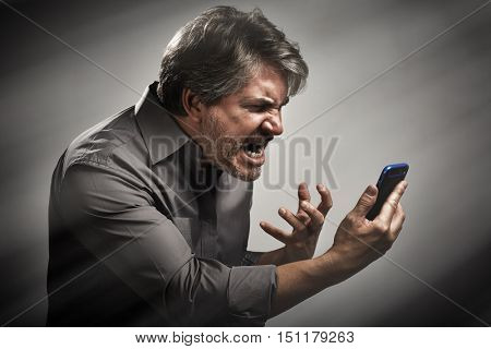 Angry screaming man with cell phone.