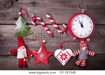 Christmas background. Clock candy canes fur tree toys and decorative dollies on aged wooden background. Flat lay.
