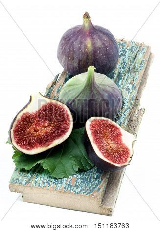 Arrangement of Fresh Ripe Figs Full Body and Halves with Leaf Cracked Wooden Planch isolated on White background