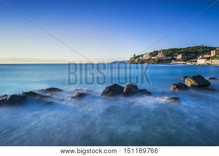 Rocks in a blue ocean on sunset Castiglioncello Tuscany Italy. Long exposure photography