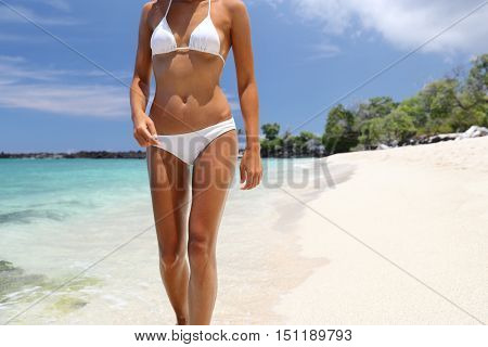 Bikini woman relaxing on tropical beach vacation. Sexy slim body unrecognizable model walking in white fashion swimsuit with toned sun tanned skin on paradise getaway destination. Suntan concept.