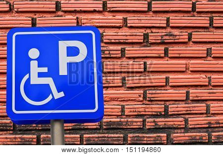 handicapped parking place sign on brick wall