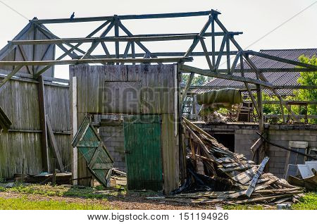 Closeup of a neglected and collapsed small wooden shed in an industrial area.