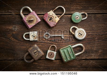 Group of old rusty padlocks on brown wooden table
