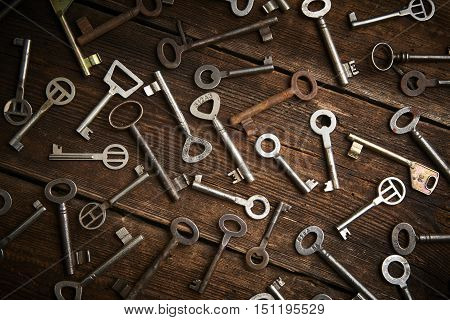 many different keys on brown wooden background.
