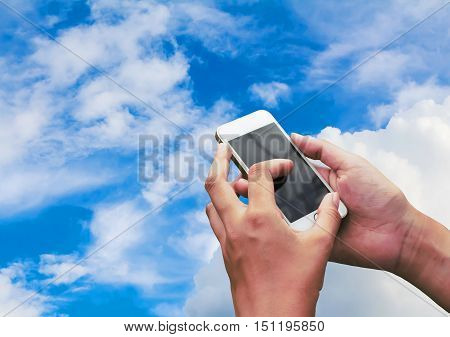 Hand hold and touch screen smart phone,on blue sky.
