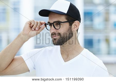 Man adjusting spectacles smiling - in town
