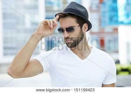 Cool guy with sunglasses tipping hat in town