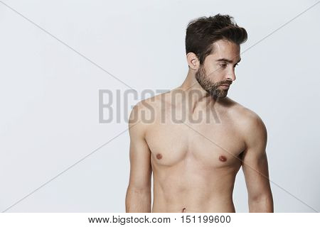Shirtless dude looking away in studio - grey background
