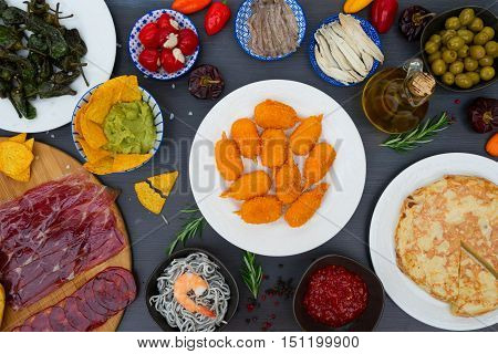 Table with plates of spanish tapas - jamon, croquetes, guacamole and olives, top view, picnic table