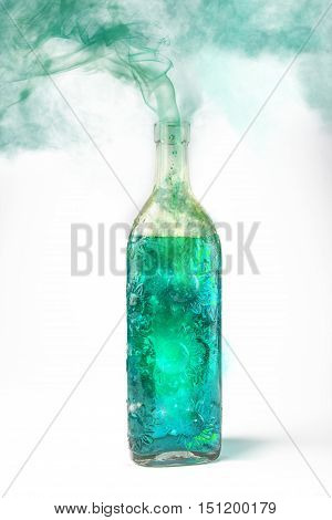 Translucent bottle with green magical potion fuming and releasing smoke
