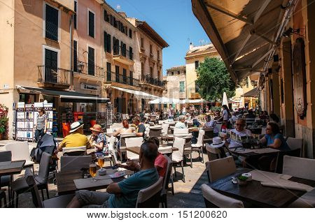 ALCUDIA MAJORCA SPAIN - May 23 2015. Crowded square of Alcudia. People relax and enjoy their drinks and food at an outdoor cafe terrace.