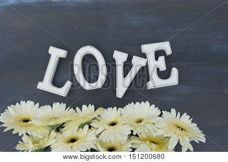 Beige gerbera flowers border on dark wood with love letters