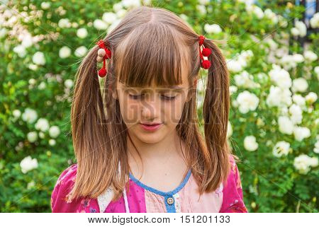 Portrait of cute pensive little girl with pigtails on garden background