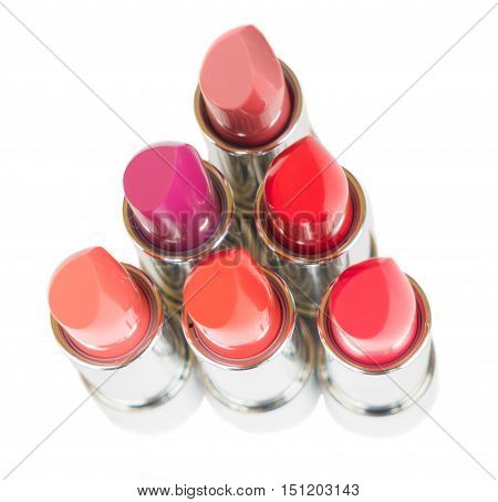 puple, pink and red shiny lipsticks isolated on white background