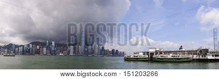 HONG KONG - May 28 2015: Panorama of Hong Kong Skyline, rain clouds and Star Ferries, May 28, 2015 in Hong Kong.