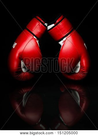 A pair of red boxing gloves,l on reflective surface