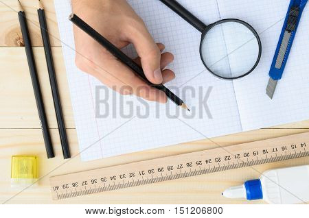 Closeup hands of man holding pencil and drawing on white paper in top view. Draftsman workplace equipped with ruler, pencils, glue, sharpener, magnifying glass.