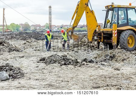 Zrenjanin Vojvodina Serbia - June 14 2015: Backhoe tractor is working on a construction site. Group of workers with shovels are digging.