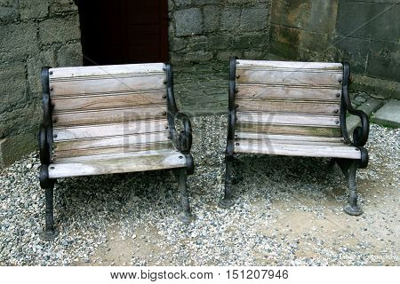 Two small wooden benches, facing the street.
