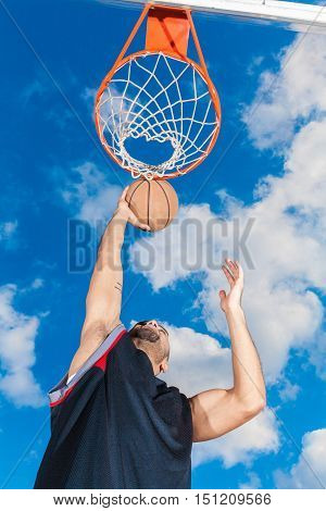 Low Angle View of Basketball Player Dunking Ball