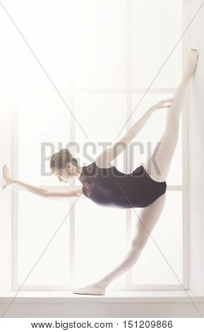 Classical Ballet dancer portrait. Beautiful graceful ballerine in black practice standing split ballet position at window background. Ballet class training, high-key soft toning. Vertical image