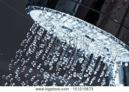 Shower Head with Water Stream on Black Background