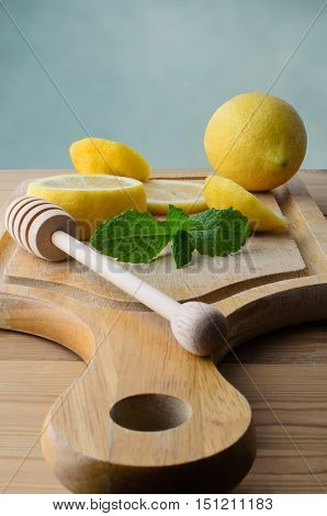 Whole and sliced lemons with mint leaves and honey drizzler on wooden chopping board with pine kitchen table below.