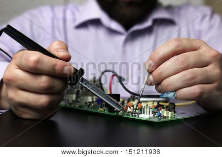 man hands chip soldering tools on a black background