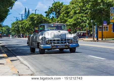 Varadero, Cuba - September 03, 2016: White blue american classic cabriolet car drivet hrough Varadero in Cuba - Serie Cuba 2016 Reportage