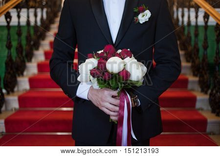 The groom with bride's bouquet meets his future wife, close-up