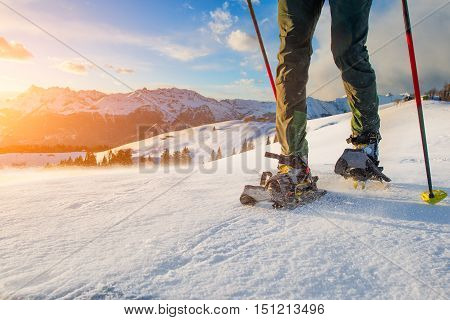 Detail of man walking with technical snowshoes in mountains