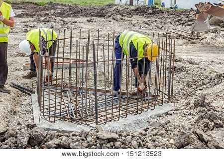 Zrenjanin Vojvodina Serbia - June 14 2015: Workers are tying rebar to make a newly constructed footing frame. Binding concrete frame