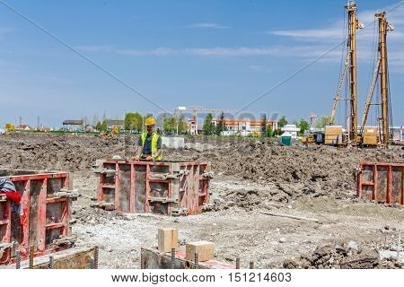 Zrenjanin Vojvodina Serbia - June 14 2015: View on building site until workers are assembly demountable wooden mold for concreting pillar base.