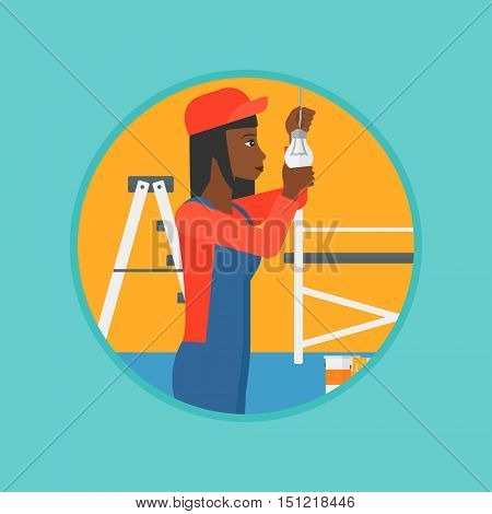 An african-american electrician twisting a light bulb. An electrician installing light in an apartment. Woman changing light bulb. Vector flat design illustration in the circle isolated on background.