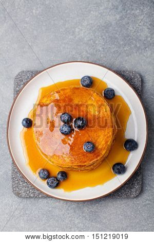 Pumpkin pancakes with maple syrup and blueberries on a plate. Grey stone background Top view Copy space