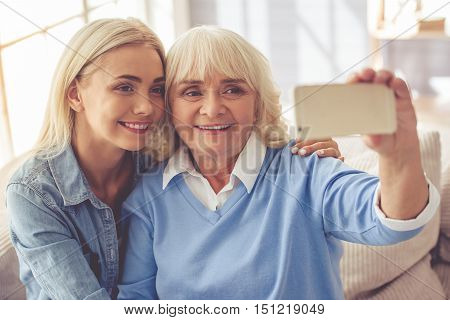 Beautiful old woman and young girl are doing selfie using a smart phone and smiling while sitting on couch at home