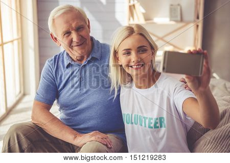 Beautiful young girl volunteer and handsome old man are doing selfie using a smart phone and smiling while sitting on couch