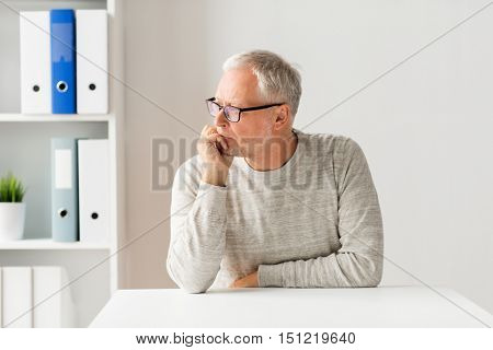 old age, problem, health care and people concept - sad senior man sitting at table at medical office