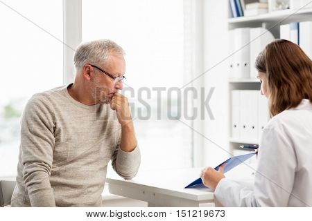 medicine, age, health care and people concept - senior man and doctor with clipboard meeting in medical office at hospital
