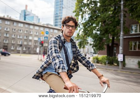 people, style, leisure and lifestyle - young hipster man with shoulder bag riding fixed gear bike on tallinn city street