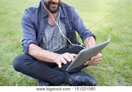 people, music, technology, leisure and lifestyle - close up of happy hipster man with tablet pc and earphones sitting on grass