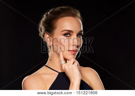 people, luxury, jewelry and fashion concept - beautiful woman in black wearing golden earrings and ring with diamonds over dark background