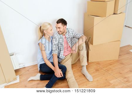 home, people, repair, moving and real estate concept - happy couple with many cardboard boxes sitting on floor at new place