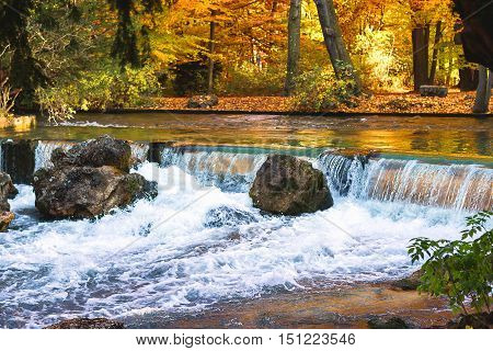 Waterfall in autumn in Munich city as background