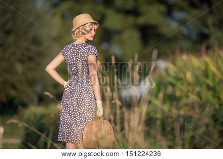 Retro 1930S Summer Fashion Woman With Blue Dress And Straw Hat Standing With Handbag In Rural Landsc
