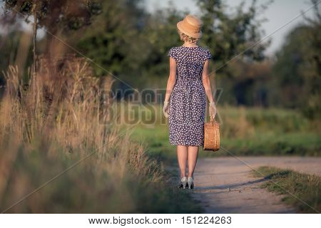 Rear View Of Vintage 1920S Summer Fashion Woman With Blue Dress And Straw Hat Standing With Handbag