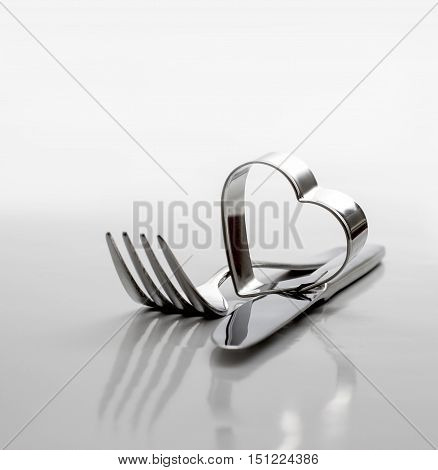 Cutlery, fork with knife and heart on grey background