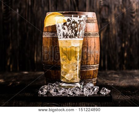 half empty glass of beer with lemon and ice with little beer barrel on the background